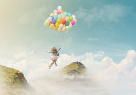 Little girl holding colorful balloons, jumping from one mountain top to the other; success/achievement concept, fantasy background with copy space