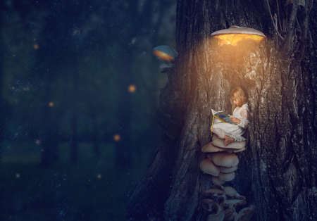 Enchanted forest - little girl sitting under the glowing mushroom, reading her book; Fantasy, nature, fairy tale; Standard-Bild