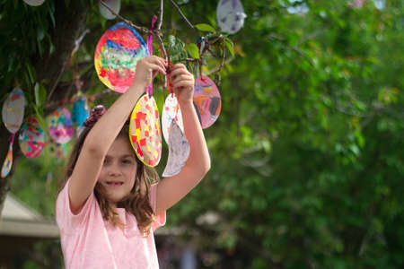 Cute little girl hanging on the tree her Easter cards in egg shape, for good luck and with good wishes