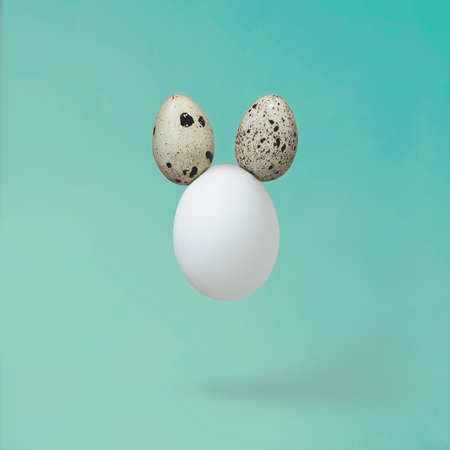 White egg with quail eggs as ears - minimal creative Easter concept Standard-Bild