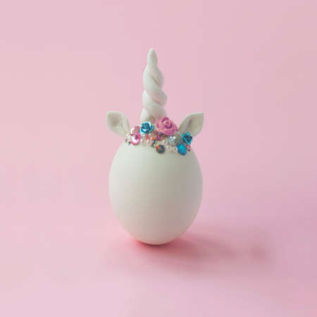 Single white egg, with unicorn decoration; Creative minimal Easter background