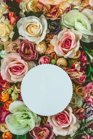 Beautiful colorful flowers wall background, with white circle greeting card with copy space; Spring, wedding, anniversary or florist greeting card