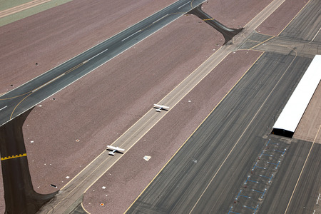 fixed wing aircraft: Two single engine airplanes on the taxiway preparing for take off