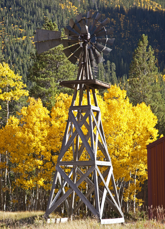 Windmill with changing colors of the Aspen Trees as a backdrop off Independence Pass in Colorado