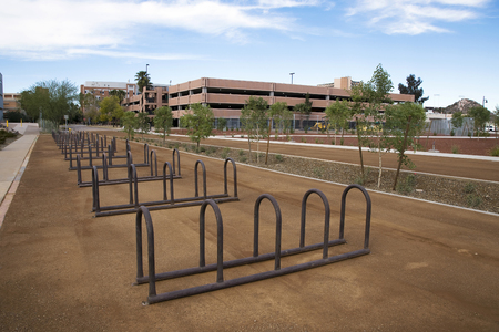 Empty Row of bike racks adjacent to light rail and campus