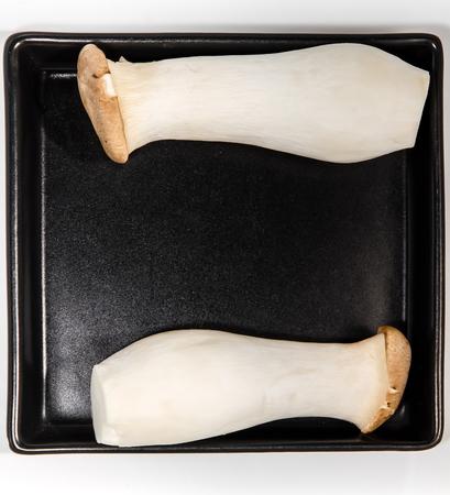 fungoid: Mushroom names Eringii on a black plate