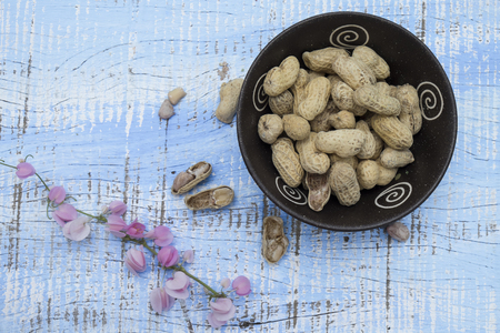 unpeeled: Unpeeled peanuts in bowl on wooden background closeup