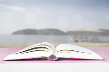 art book: Open book on pink table with green bokeh abstract background