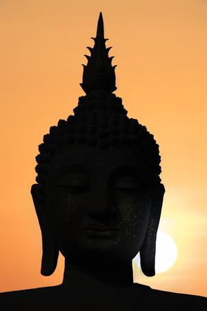 Silhouette public big white Buddha, sunset in Thailand