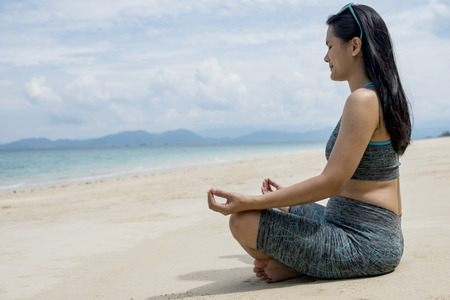 Young beautiful healthy woman making meditation on the beach Stock Photo