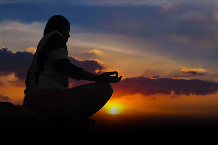 silhouette of a woman meditating in a yoga pose on the beach at sunset