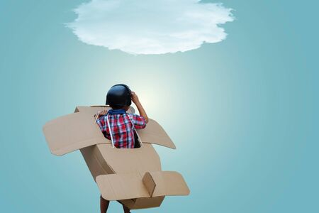 Little boy in a cardboard airplane. Child is pretending to be a pilot. Travel, freedom and imagination concept