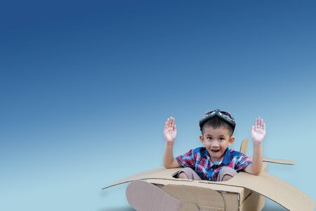 Little boy in a cardboard airplane on blue sky background. Child is pretending to be a pilot. Travel, freedom and imagination concept Stockfoto