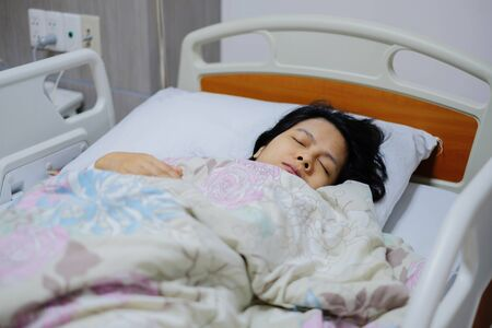 Sick woman in hospital. Woman sleep on bed and she is on a drip receiving a saline solution