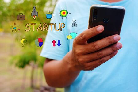 Man is using mobile phone. Startup business concept with young man holding his smartphone outside in the park.