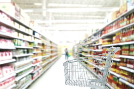 Supermarket aisle with empty shopping cart. Abstract blurred photo of store with trolley in department store bokeh background. Reklamní fotografie