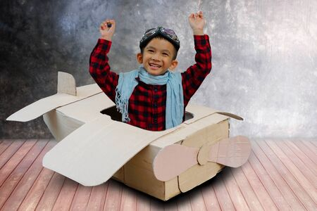 Little boy in a cardboard airplane. Child is pretending to be a pilot. Kid playing at home. Travel, freedom and imagination concept