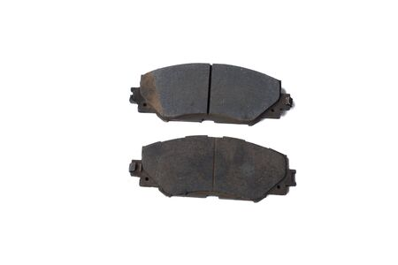 Old rusty used car brake pads on a white background.