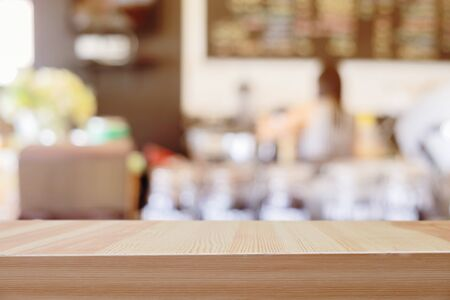 Mesa de madera delante de fondo abstracto bokeh borrosa de cafetería.
