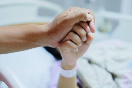Close up focus on the Shake hands of a patient sick encourage encouragement on the bed in hospital ward. Healthcare concept.