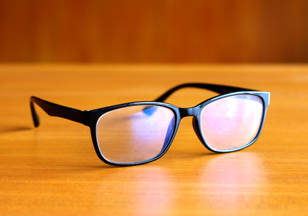 optometrist: the glasses on wooden background