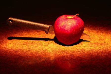 tomando refresco: Un cuchillo en una manzana roja  Foto de archivo