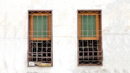 latticework: Vintage windows protected by latticework on sandstone wall Stock Photo