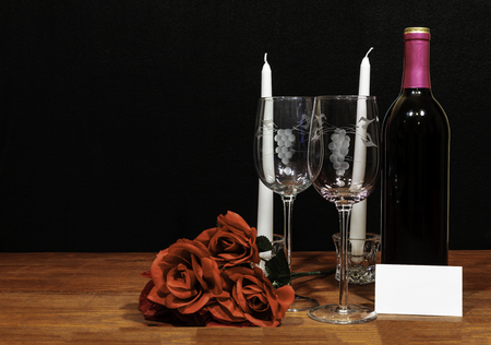 Beautiful etched wine glasses and bottle of red wine, white candles and red roses on wooden table with name tag on dark background. Valentines, Mothers Day, Easter, Christmas, Wedding Concepts Stok Fotoğraf