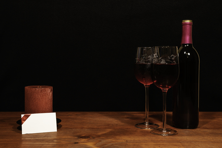 Beautiful etched wine glasses and bottle of red wine, red candle on wooden table with name tag on dark background. Valentines, Mothers Day, Easter, Christmas, Wedding Concepts