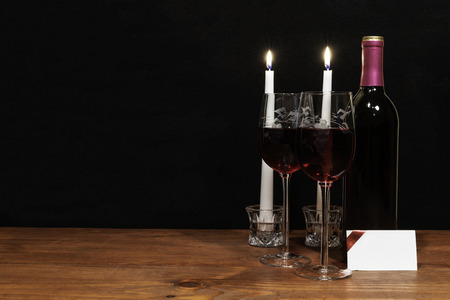 Beautiful etched wine glasses and bottle of red wine, white candles, on wooden table with name tag on dark background. Valentines, Mothers Day, Easter, Christmas, Wedding Concepts Stok Fotoğraf