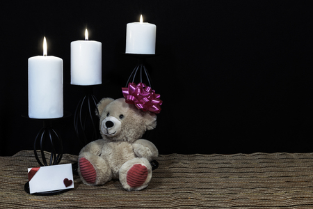 Cudlely teddy bear with pink bow on head, white candles perched on black candle holders on mesh place mat and wooden table with card and dark background. Valentines, Mothers Day, Easter, Christmas, Wedding Concepts