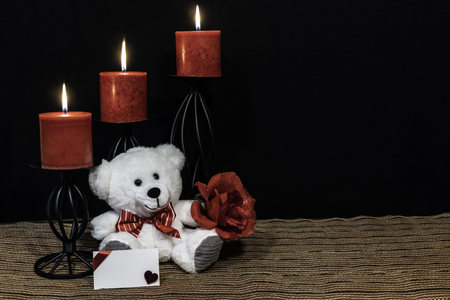 Cudlely teddy bear with red bow tie, red rose, red candles perched on black candle holders on mesh place mat and wooden table with card and dark background. Valentines, Mothers Day, Easter, Christmas, Wedding Concepts