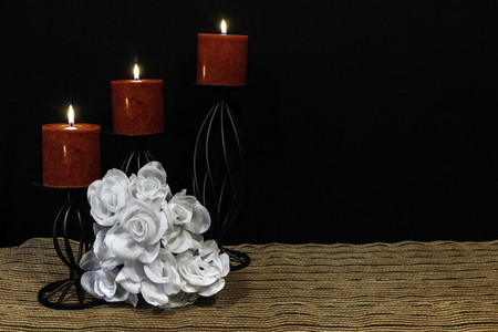 Beautiful bouquie of white roses, red candles perched on black candle holders on mesh place mat and wooden table with card and dark background. Valentines, Mothers Day, Easter, Christmas, Wedding Concepts