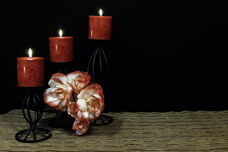 Beautiful orange and white roses, red candle perched on black candle holders on mesh place mat and wooden table with dark background. Valentines, Mothers Day, Easter, Christmas, Wedding Concepts