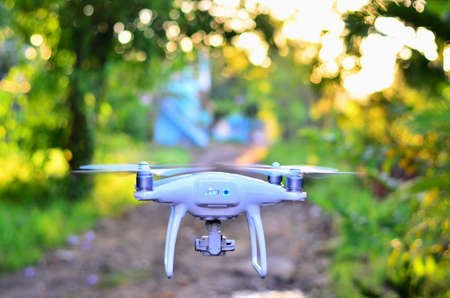 White drone take off from land and flying for take aerial photo. at sunrise beautiful bokeh background. Editorial
