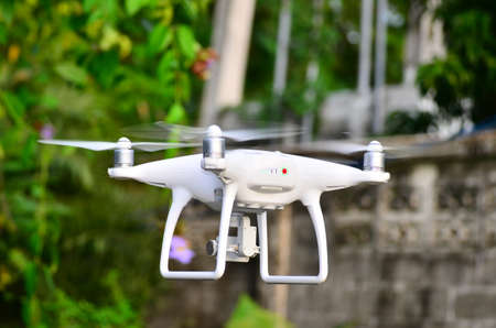 drone take off from land and flying for take aerial photo. at sunrise morning. Trees background.