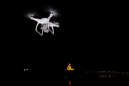 White drone take off from land and flying for take aerial photo. at dark night big monk river side. Stock Photo