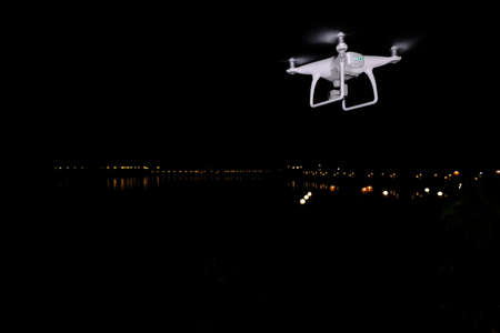 White drone take off from land and flying for take aerial photo. at dark night river side.