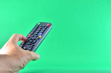 Remote control for satellite receiver box tv hd Thailand. finger push bottom. Isolate green background. Stock Photo