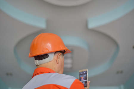 foreman working job in room. see smart phone. Stock Photo
