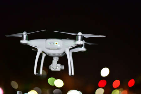 4 rotor drone take off from land and flying for take aerial photo. at might blurred light bokeh background.
