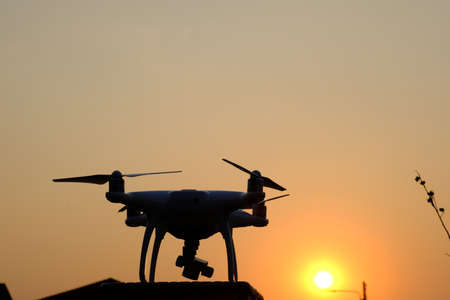 Silhouette white aircraft drone take off from land and flying for take aerial photo. at sunset evening orange blue sky. Stock Photo
