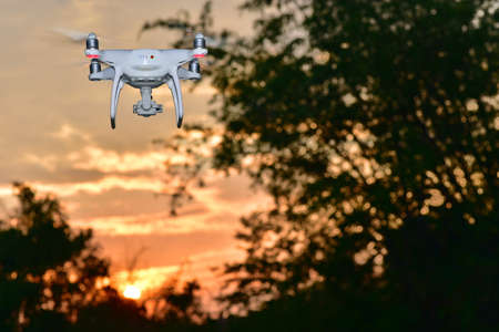 Silhouette White drone flying for take aerial photo. at sunset evening orange sky.