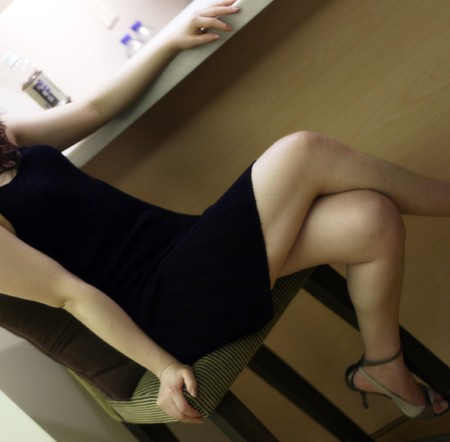 slut: cute girl sit on chair with great hooker legs in a shift dress Stock Photo