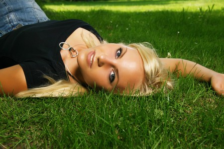 Blonde German girls lays down in the summer grass