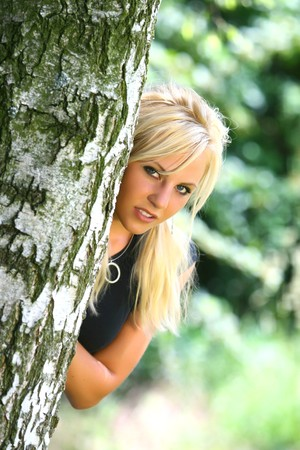 Perfect Blond German Girl behind the tree in nature photo