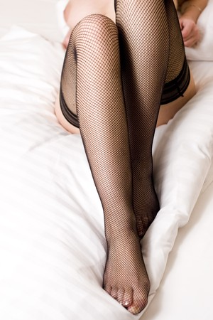 slut: Long legs in stockings from a nice prostitute which is laying down on the bed. Stock Photo