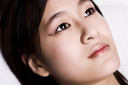 Young Asian girl is doing a wellness day and will getting a nice tender pampering massage and treatment. She has perfect make-up and beautiful skin Stock Photo - 4257577