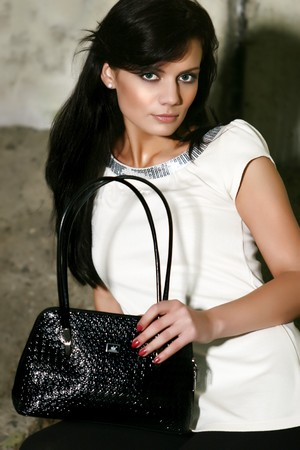 Beautiful girl with black hair is holding a cute crocodile leather handbag. She has nice green eyes, perfect skin, lovely make-up and is sitting in front of the concrete wall. Photo is made outdoor.