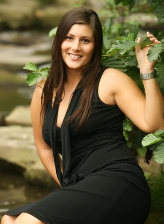 busty: Mooie lachende meisje in zwarte jurk. Zeer aantrekkelijk met lang haar. Zittend in de natuur voor een mooi beekje.